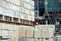 Trabajadores de construcción que apilan el bloque de prueba de carga del mantener en el emplazamiento de la obra Foto de archivo libre de regalías