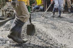 Trabajadores de construcción que cementan el camino Foto de archivo