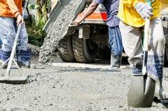 Trabajadores de construcción que cementan el camino Imagen de archivo libre de regalías