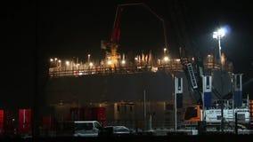 Trabajadores de construcción que están construyendo un edificio grande durante noche con las porciones de soldar almacen de metraje de vídeo