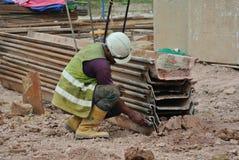 Trabajadores de construcción que examinan la pila de hoja Imagen de archivo