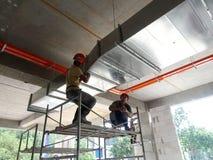 Trabajadores de construcción que instalan el conducto del aire acondicionado fotos de archivo