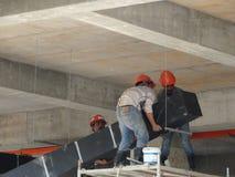 Trabajadores de construcción que instalan el conducto del aire acondicionado fotografía de archivo
