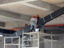 Trabajadores de construcción que instalan el conducto del aire acondicionado imagen de archivo libre de regalías