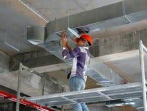 Trabajadores de construcción que instalan el conducto del aire acondicionado foto de archivo libre de regalías