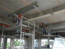 Trabajadores de construcción que instalan el conducto del aire acondicionado imagenes de archivo