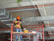 Trabajadores de construcción que instalan la bandeja de cable eléctrico y que hacen trabajos del cableado fotografía de archivo libre de regalías