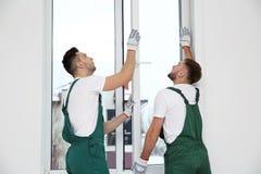 Trabajadores de construcción que instalan la ventana plástica foto de archivo