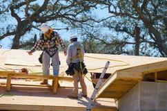 Trabajadores de construcción que llevan la cuerda de salvamento del arnés de seguridad Fotografía de archivo libre de regalías