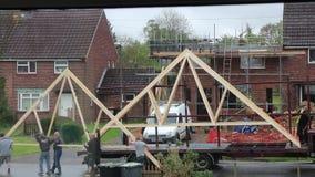 Trabajadores de construcción que mueven haces de tejado almacen de video