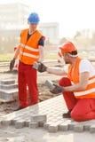 Trabajadores de construcción que pavimentan la calle fotos de archivo libres de regalías