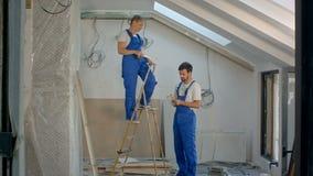 Trabajadores de construcción que renuevan el edificio de apartamentos almacen de video