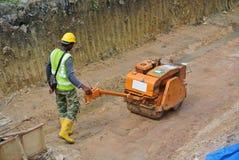 Trabajadores de construcción que usan el compresor del rodillo del bebé Foto de archivo libre de regalías