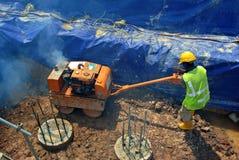 Trabajadores de construcción que usan el compresor del rodillo del bebé Imagen de archivo libre de regalías