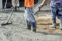 Trabajadores de construcción que vierten el cemento en el camino Imagen de archivo libre de regalías