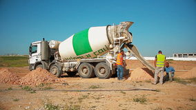 Trabajadores de construcción que vierten el hormigón a un agujero en la tierra del camión del mezclador concreto en el emplazamie almacen de metraje de vídeo