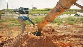 Trabajadores de construcción que vierten el hormigón a un agujero en la tierra del camión del mezclador concreto en el emplazamie metrajes