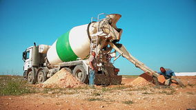Trabajadores de construcción que vierten el hormigón a un agujero en la tierra del camión del mezclador concreto en el emplazamie almacen de video