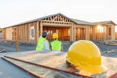 Trabajadores de construcción de sexo masculino y de sexo femenino en el nuevo sitio casero fotos de archivo