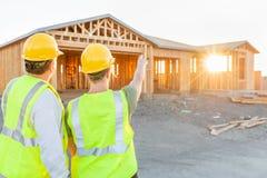 Trabajadores de construcción de sexo masculino y de sexo femenino en el nuevo sitio casero fotografía de archivo