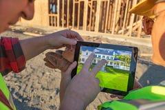 Trabajadores de construcción de sexo masculino y de sexo femenino que revisan la casa en el ordenador foto de archivo libre de regalías