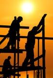 Trabajadores de construcción bajo un sol ardiente caliente Imagen de archivo