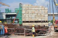 Trabajadores de construcción que apilan el bloque de prueba de carga del mantener en el emplazamiento de la obra Imagenes de archivo