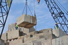Trabajadores de construcción que apilan el bloque de prueba de carga del mantener en el emplazamiento de la obra Imagen de archivo