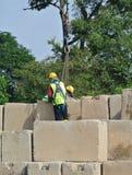 Trabajadores de construcción que apilan el bloque de prueba de carga del mantener en el emplazamiento de la obra Imágenes de archivo libres de regalías