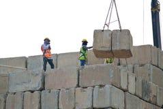 Trabajadores de construcción que apilan el bloque de prueba de carga del mantener en el emplazamiento de la obra Foto de archivo