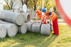 Trabajadores de construcción que ruedan los tubos concretos Fotos de archivo libres de regalías