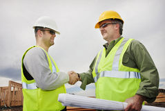 Trabajadores de construcción que sacuden las manos Imágenes de archivo libres de regalías