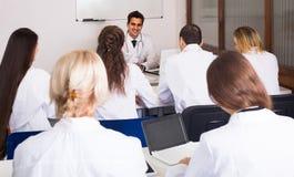 Trabajadores de la atención sanitaria durante programa educativo en escuela imagen de archivo