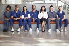 Trabajadores de la atención sanitaria que se sientan en un hospital moderno, ángulo bajo imagen de archivo