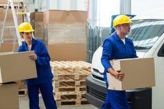 Trabajadores de la entrega que descargan las cajas de cartón del enchufe de la plataforma imagenes de archivo