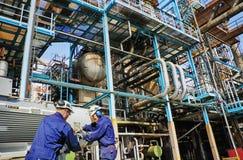 Trabajadores de la industria dentro de la refinería del petróleo y gas Imagen de archivo