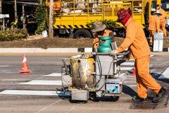 Trabajadores de la marca de camino en el trabajo bajo chamuscadura de Sun imagen de archivo libre de regalías