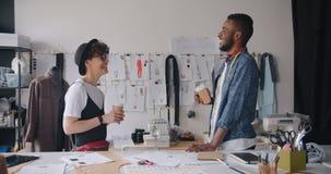 Trabajadores de la muchacha y del individuo del estudio de la moda que hablan sosteniendo el café para ir a relajarse almacen de metraje de vídeo