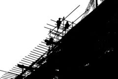 Trabajadores de la silueta que construyen el edificio en el emplazamiento de la obra ilustración del vector