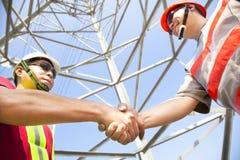 Trabajadores de la torre de la línea eléctrica fotos de archivo