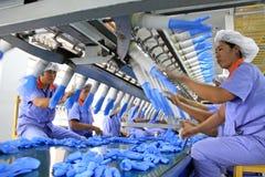Trabajadores de sexo femenino en la producción de los guantes del butadieno del acrilonitrilo Foto de archivo libre de regalías