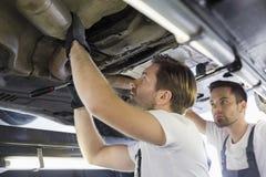 Trabajadores de sexo masculino de la reparación que examinan el coche en taller Imágenes de archivo libres de regalías