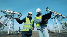 Trabajadores de sexo masculino que discuten un proyecto cerca de torres de perforación de aceite, cierre para arriba metrajes