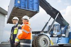 Trabajadores de sexo masculino y de sexo femenino que hacen una pausa el vehículo de la carga en yarda de envío Imagen de archivo libre de regalías