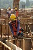Trabajadores de una construcción que fabrican la barra del refuerzo Fotografía de archivo libre de regalías