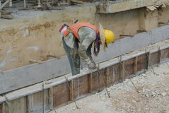 Trabajadores de una construcción que instalan encofrado del haz de tierra Fotos de archivo libres de regalías