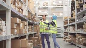 Trabajadores de Warehouse comunicar y realizar el código de barras del escáner de la contabilidad metrajes
