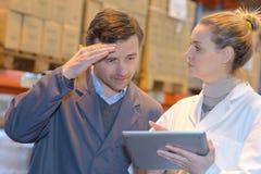 Trabajadores de Warehouse en taller usando la tableta digital imagen de archivo