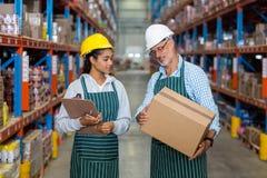 Trabajadores de Warehouse que comprueban la caja de cartón imagenes de archivo