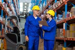 Trabajadores de Warehouse que discuten con el tablero imagen de archivo libre de regalías